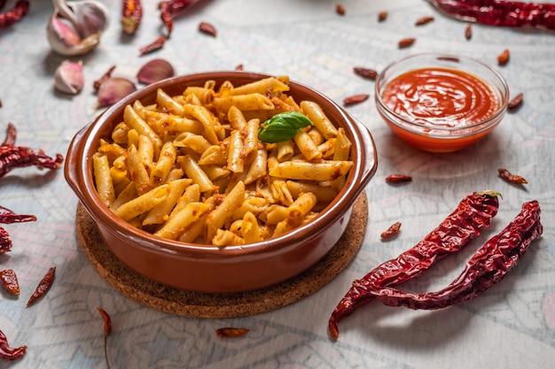 Makkaroni mit rotem pesto in einer tonpfanne mit einigen zutaten auf einem weißen tisch.