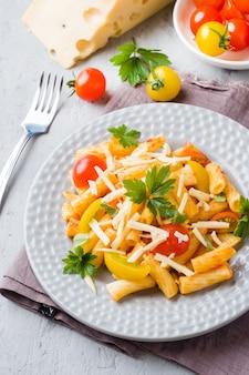 Makkaroni, nudeln in tomatensauce und käse in einer platte auf einem woode