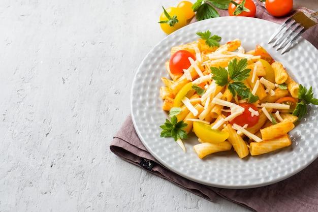 Makkaroni, teigwaren in tomatensauce und käse in einer platte auf einem holztisch