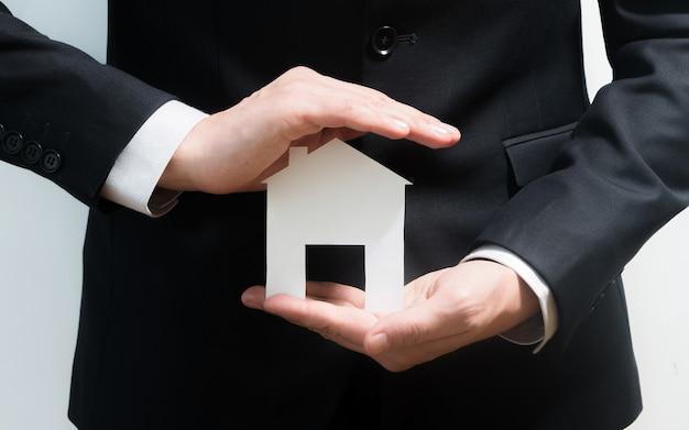 Makler, immobilienmakler, der papiermodell eines hauses hält