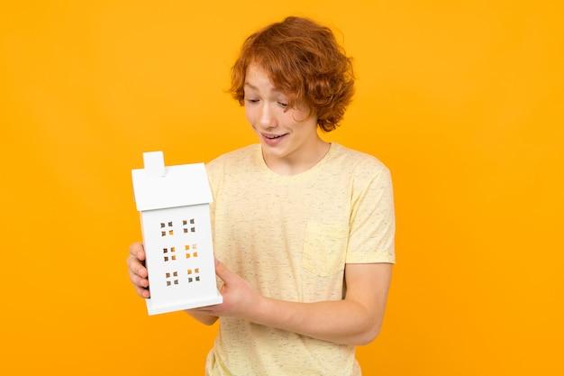 Makler kerl hält ein hausmodell in seiner hand auf einem gelben hintergrund mit kopienraum