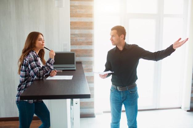 Makler, makler oder vermieter zeigt einer jungen frau eine wohnung. sie wird einen mietvertrag mit ihm unterschreiben.