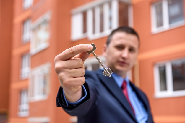Makler mit schlüssel aus neuer wohnung in der nähe von neuem haus