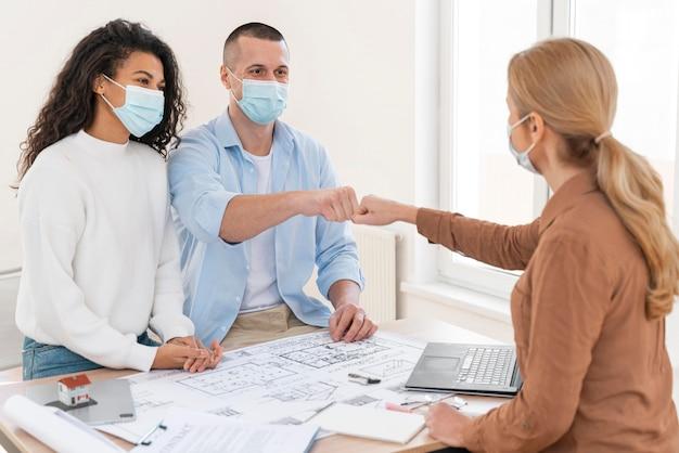 Maklerin mit medizinischer maskenfaust, die paar über tisch mit hausplänen stößt
