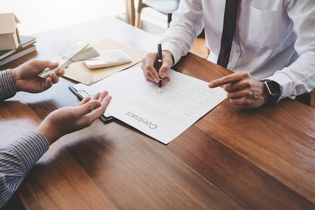 Maklervertreter präsentiert und konsultiert den kunden detailliert, um die entscheidung über ein wohnungsbaudarlehen zu treffen, um eine formularvereinbarung zu unterzeichnen