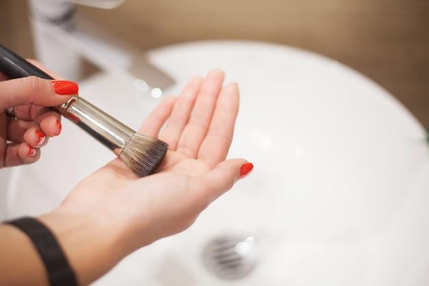 Makr up pinsel. frau, die schmutzige make-upbürste mit seife und schaum in der wanne wäscht