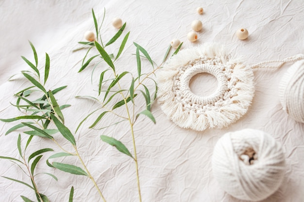 Makramee-baumwolldekor. natürliche materialien - baumwollfaden, holzperlen. öko-dekorationen, ornamente, handgemachtes dekor. platz kopieren