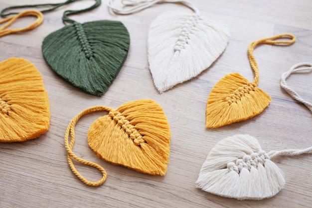 Makramee-blätter in gelber, grüner und natürlicher farbe auf dem holzhintergrund. baumwollseil-dekor makramee, um ihr zuhause gemütlicher und einzigartiger zu machen.