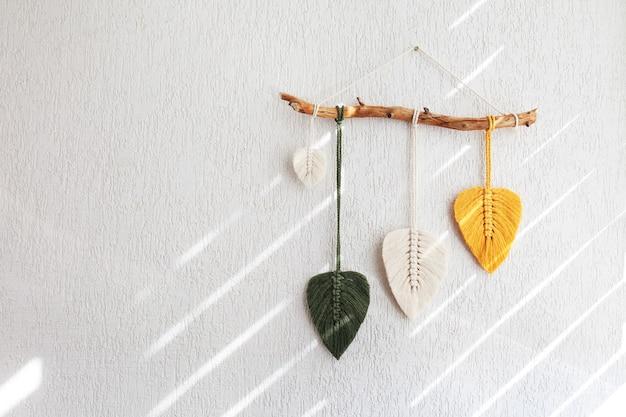 Makramee blätter wandbehang in gelb, weiß und grün und naturfarben am holzstab. baumwollseil-dekor makramee machen ihr zimmer gemütlicher und einzigartiger. platz kopieren
