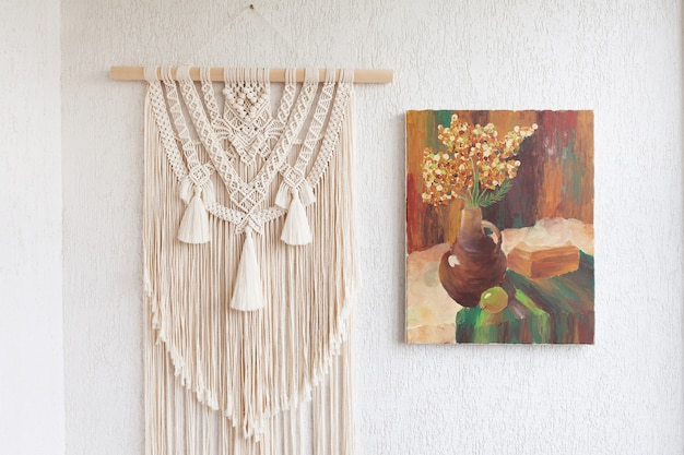 Makramee. dekoration für den innenraum. innenarchitektur mit beiger schöner makramee- und leinwandmalerei. konzept der gemütlichen wohnkultur.
