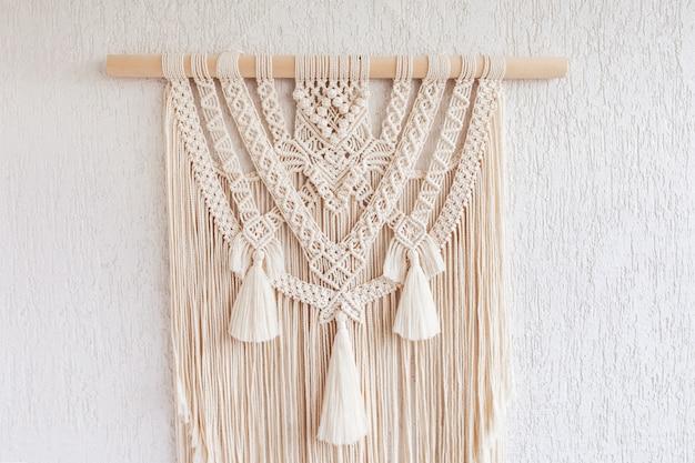Makramee. dekoration für den innenraum. innenarchitektur mit beiger schöner makramee-wandübergabe. konzept der gemütlichen wohnkultur.