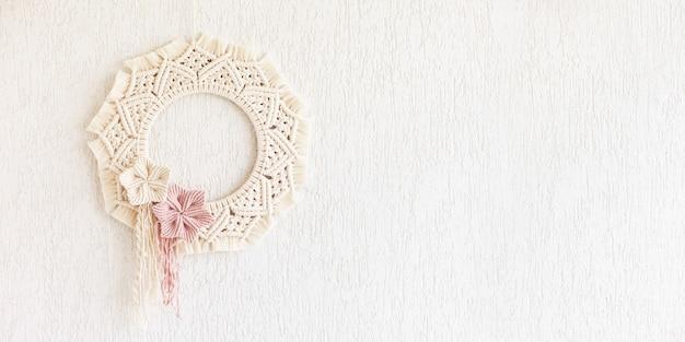 Makramee-kranz mit baumwollblumen auf einer weißen dekorativen gipswand. natürlicher baumwollfaden und seil. öko-dekor für zu hause. kreatives frauenhobby. platz kopieren. banner