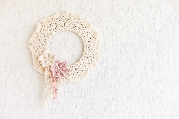 Makramee-kranz mit baumwollblumen auf weißer dekorativer putzwand