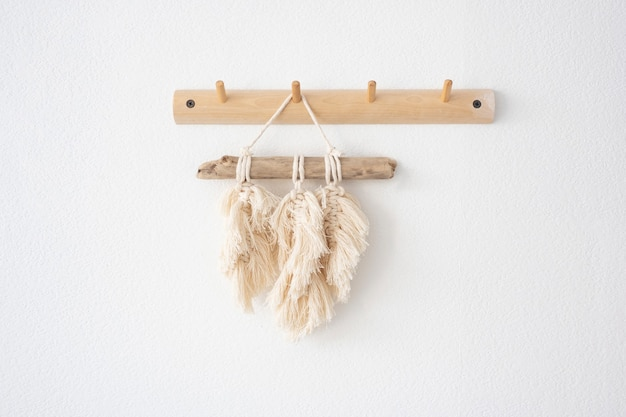 Makramee-paneele hängen an einem holzhaken an einer hellen wand.