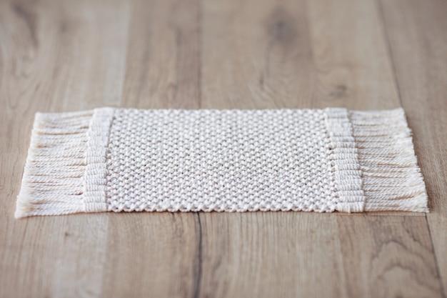 Makramee-teppich auf holztisch oder teppich auf dem boden. handgefertigte beige makramee. makramee-textur, eco-freundlich, modernes stricken.