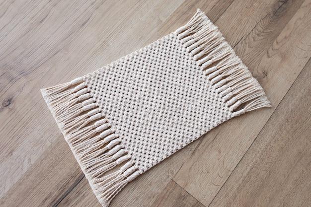 Makramee-teppich auf holztisch oder teppich auf dem boden. handgefertigter beiger makramee-teppich. makramee-textur, eco-freundlich, modernes stricken.