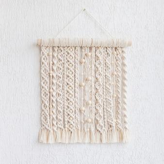 Makramee wandbehang mit holzperlen. wandpaneel aus baumwollfäden in natürlicher farbe. makramee-technik für öko-wohnkultur. moderne makramee-wandbehänge sorgen für eine gemütliche atmosphäre. speicherplatz kopieren