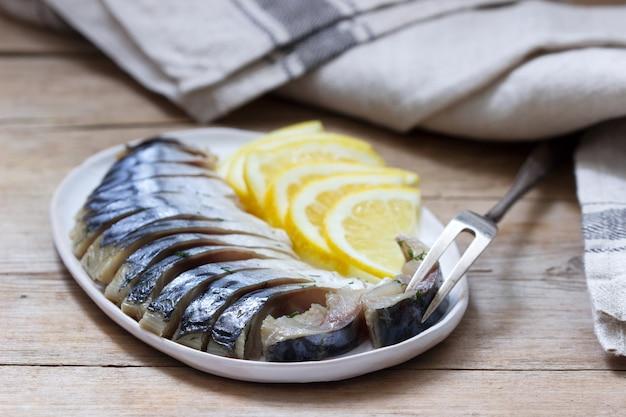 Makrelen-glavrax mit zitronenscheiben auf einer holzoberfläche
