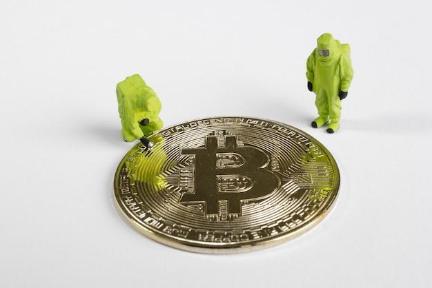 Makro-bergarbeiterfiguren, die auf bitcoin schauen. virtual cryptocurrency mining-konzept