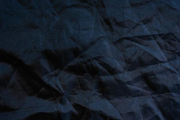 Makro der beschaffenheit eines geknitterten plastikgewebes des schwarzen hintergrundes