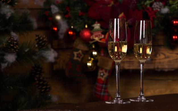 Makro goldener champagner auf eleganten flötengläsern auf dem holztisch mit weihnachtsdekor-hintergrund.