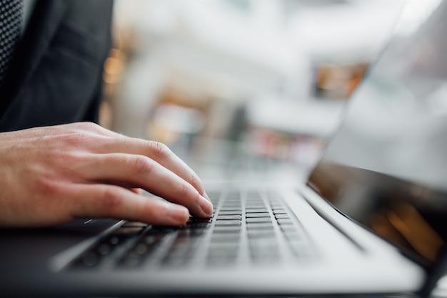 Makro, hände auf einer laptoptastatur. computer-laptop-tastatur, die handtechnologie-internetarbeitskonzept tippt