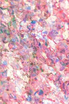 Makro-nahaufnahme des zerschmetterten rosa holographischen konfetti-strukturierten hintergrunds