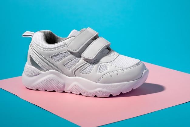 Makro-seitenansicht eines weißen unisex-sneakers mit klettverschlüssen zum einfachen beschlagen auf einem geometrischen quadrat...