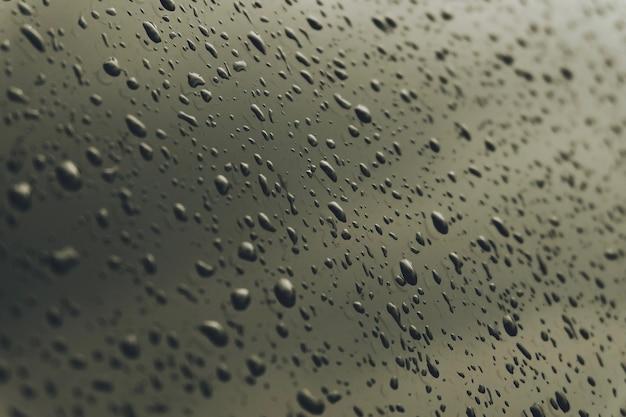 Makro transparenter tautropfen auf spiegel. nahaufnahme des regenwassers. stimmungsvoller ton.