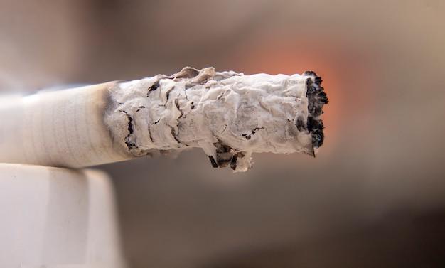 Makroansicht der brennenden zigarette mit rauche.