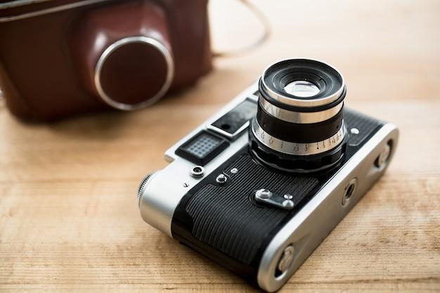 Makroansicht der manuellen retro-kamera und der ledertasche, die auf dem tisch liegen