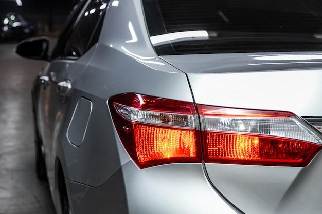 Makroansicht des modernen silbernen autoxenonlampenrücklichts, stoßdämpfer, hintere kofferraumklappe. äußeres eines modernen autos