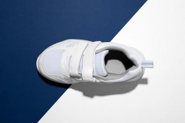 Makroansicht von oben auf einem weißen kindersneaker mit klettverschlüssen zum einfachen beschuhen auf einem trendigen blauen und ...