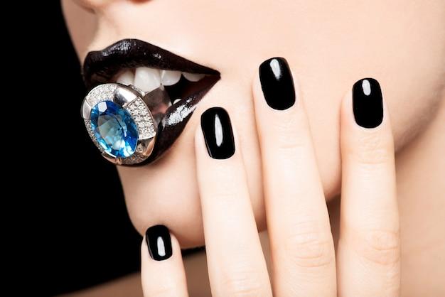 Makroaufnahme der lippen und nägel einer frau, die hell schwarz lackiert sind