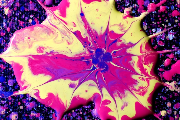 Makroaufnahme einer abstrakten mischung der bunten acrylfarbe spritzt auf einem schwarzen hintergrund