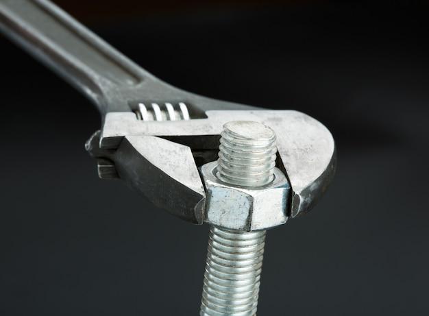 Makroaufnahme einer schraube und eines schraubenschlüssels isoliert auf schwarz