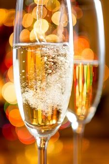 Makroaufnahme von champagnerblasen gegen funkelnde lichter