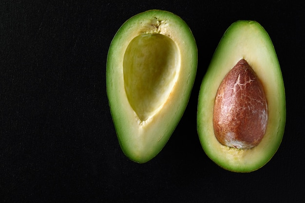 Makroaufnahme von frischen avocados, die auf dem schwarzen hintergrund halbiert werden.