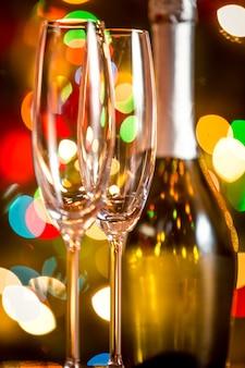 Makroaufnahme von zwei gläsern und einer flasche champagner gegen funkelnde weihnachtsbeleuchtung