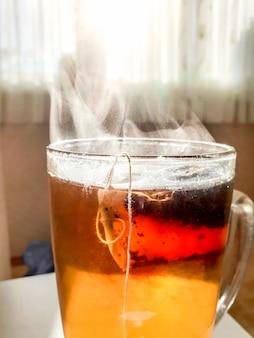 Makrobild von dampf, der aus heißem tee in glastasse gegen helles sonnenlicht fließt