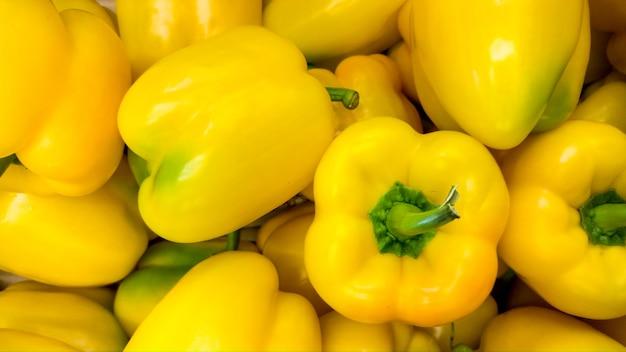 Makrobild von vielen frischen gelben paprikas oder paprika. textur oder muster von frischem reifem gemüse