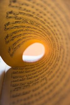 Makrodetail des aufgerollten musikalischen briefpapiers