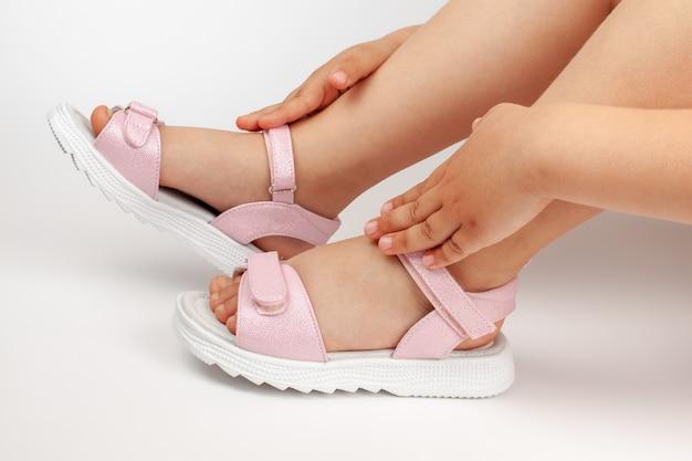 Makrodetails rosa kindersandalen an den mädchenfüßen eines kindes, das auf einem weißen gegossenen hintergrund sitzt