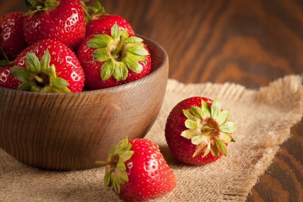 Makrofoto der frischen reifen roten erdbeere in einer hölzernen schüssel auf rustikalem hintergrund. bio-naturprodukte.