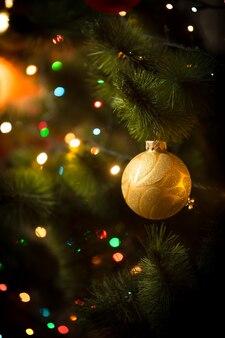 Makrofoto der goldenen kugel und der hellen girlande am weihnachtsbaum
