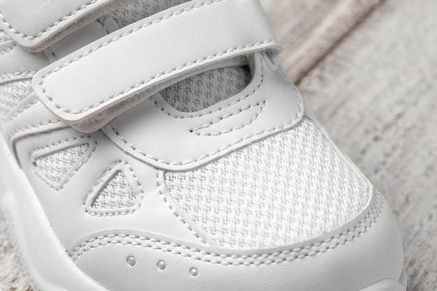 Makrofoto des sneakers foto eines weißen kindersneakers aus leder und stoff mit klett...