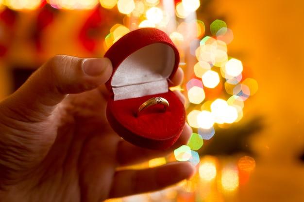 Makrofoto eines mannes, der einen goldenen ring in einer schachtel gegen einen geschmückten weihnachtsbaum präsentiert