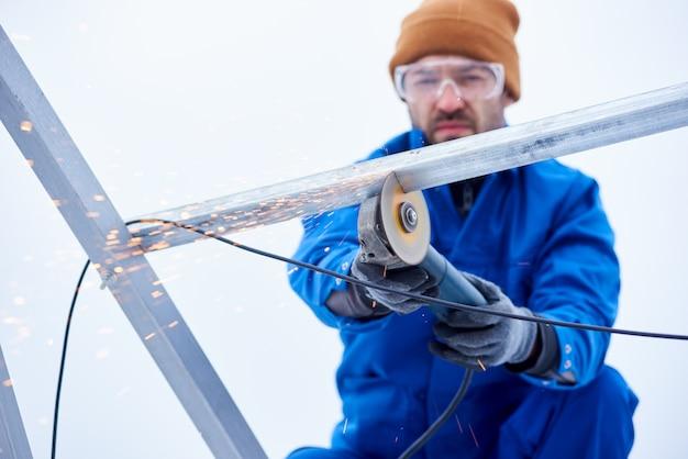 Makrofotografie ein mann mit bulgaren schneidet den rahmen eines panels, um eine solarbatterie zu installieren. konzentrieren sie sich auf das bulgarische werkzeug