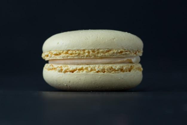 Makrone auf dunklem hintergrund, beige französische plätzchen macarons.
