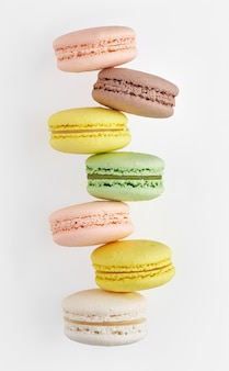 Makrone. bunter kuchen macaron mit pastelltönen chaotisch gestapelt in einer reihe auf weißer wand. draufsicht auf mandelkekse.
